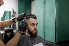El hombre elegante con una barba se sienta en una peluquería de caballeros El peluquero en guantes negros hace diseñar y la rocia foto de archivo