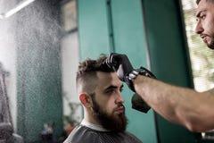 El hombre elegante con una barba se sienta en una peluquería de caballeros El peluquero en guantes negros hace la rociadura para  foto de archivo libre de regalías