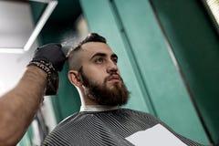 El hombre elegante con una barba se sienta en una peluquería de caballeros El peluquero en guantes negros hace la rociadura para  imagen de archivo