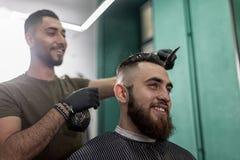 El hombre elegante con una barba se sienta y sonríe en una peluquería de caballeros El peluquero en guantes negros hace la rociad fotos de archivo libres de regalías