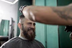 El hombre elegante con una barba se sienta y sonríe en una peluquería de caballeros El peluquero en guantes negros hace la rociad foto de archivo libre de regalías