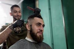 El hombre elegante con una barba se sienta y sonríe en una peluquería de caballeros El peluquero en guantes negros hace la rociad imagen de archivo