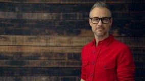 El hombre elegante en camisa roja usando la tableta sonríe almacen de metraje de vídeo