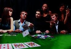 El hombre elegante en traje negro dobla dos tarjetas en póker del casino en Las Vegas sobre negro fotos de archivo