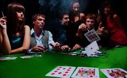 El hombre elegante en traje negro dobla dos tarjetas en póker del casino en Las Vegas sobre negro foto de archivo libre de regalías