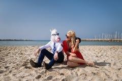 El hombre elegante en traje y máscara divertida se sienta con la mujer joven en la playa Fotos de archivo libres de regalías