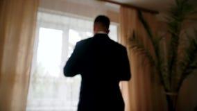 El hombre elegante en una cerradura del traje abotona en su chaqueta almacen de video
