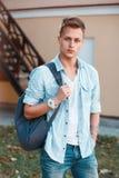 El hombre elegante joven en dril de algodón viste con una mochila que camina en th Fotografía de archivo