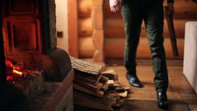 El hombre elegante joven en lanzar hecho punto del suéter de madera abre una sesión la chimenea en casa El varón caucásico irreco metrajes