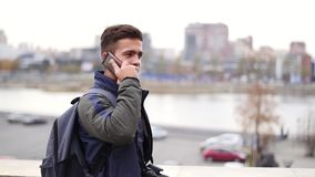 El hombre elegante joven habla en el teléfono y sonríe en la cámara lenta de la ciudad almacen de video