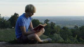 El hombre elegante lee un libro en un encintado de una plataforma de observación en el slo-MES almacen de metraje de vídeo