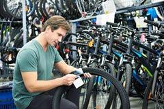 El hombre elige el neumático para bike en tienda de los deportes Imagen de archivo