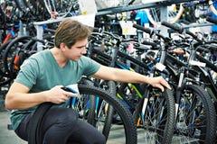 El hombre elige el neumático para bike en tienda de los deportes Foto de archivo libre de regalías