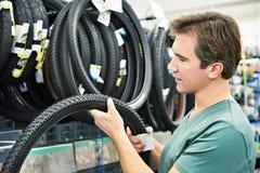 El hombre elige el neumático para bike en tienda de los deportes Imagen de archivo libre de regalías