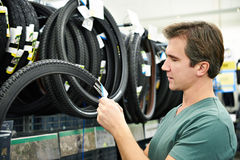 El hombre elige el neumático para bike en tienda de los deportes Fotos de archivo libres de regalías