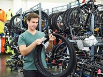 El hombre elige el neumático para bike en tienda de los deportes Fotografía de archivo libre de regalías