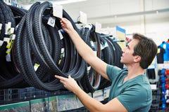 El hombre elige el neumático para bike en tienda de los deportes Imágenes de archivo libres de regalías
