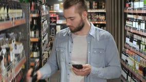 El hombre elige la cerveza en la alameda almacen de video