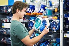 El hombre elige la máscara para el buceo con escafandra en tienda Imagen de archivo libre de regalías