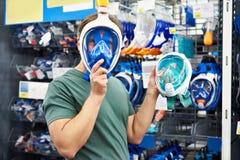 El hombre elige la máscara para el buceo con escafandra en tienda Fotografía de archivo