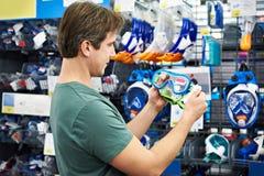 El hombre elige la máscara para el buceo con escafandra en tienda Imagenes de archivo