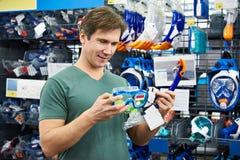 El hombre elige la máscara para el buceo con escafandra en tienda Foto de archivo