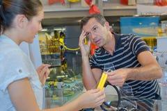 El hombre elige la máscara para el buceo con escafandra en tienda Fotos de archivo libres de regalías