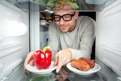 El hombre elige la verdura en vez de la carne Imagen de archivo libre de regalías