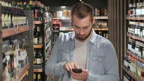 El hombre elige las bebidas en el supermercado metrajes