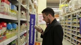 El hombre elige productos en el supermercado almacen de metraje de vídeo