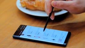 El hombre elige un reloj como regalo en una pantalla del smartphone en una tienda en l?nea se sienta en un caf? metrajes