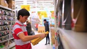 El hombre elige y compra las sustancias químicas del automóvil en almacen de metraje de vídeo