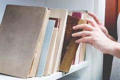 El hombre eligió el libro del estante Foto de archivo libre de regalías