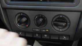 El hombre empuja el botón automático de la recirculación manualmente del aire en el coche automóvil almacen de video