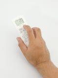 El hombre empuja la aire-condición teledirigida del botón manualmente Fotos de archivo libres de regalías
