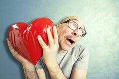 El hombre en amor sostiene una almohada roja de la forma del corazón Fotografía de archivo libre de regalías
