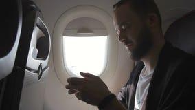 El hombre en el avión sostiene la videoconsola en sus manos y juegos con el entusiasmo almacen de metraje de vídeo