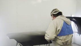 El hombre en bata y respirador protectores está pintando el detalle del coche en servicio almacen de video