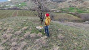 El hombre en calor rojo está caminando en el abejón aéreo de la primavera de la montaña de las colinas de la forma de vida tempra almacen de metraje de vídeo