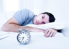 El hombre en cama con los ojos abrió insomnio sufridor y fotografía de archivo