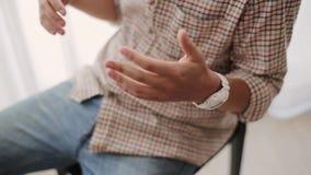 El hombre en camisa de tela escocesa con el reloj blanco, sentándose en silla hace nervioso el gesto desamparado, reloj del tacto almacen de metraje de vídeo