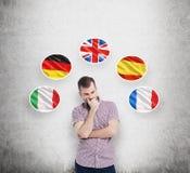 El hombre en camisa sport se sostiene la barbilla y piensa en qué lengua a estudiar Italiano, alemán, Reino Unido, español y fran Foto de archivo libre de regalías