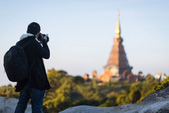 El hombre en capa tomó una foto del templo en la montaña fotografía de archivo