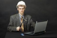 El hombre en casco con el martillo repara el ordenador Imagen de archivo libre de regalías