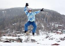 El hombre en casco del esquí salta en la montaña Imagen de archivo libre de regalías
