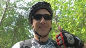 El hombre en casco disfruta de viaje y muestra la bicicleta fresca del montar a caballo de la muestra almacen de metraje de vídeo