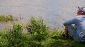 El hombre en casquillo se sienta debajo de un ?rbol en la orilla del agua del lago y de las bebidas almacen de metraje de vídeo