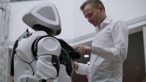 El hombre en el centro comercial comunica con un consejero del robot Vendedor moderno de la tienda y del robot El robot ayuda a u almacen de metraje de vídeo
