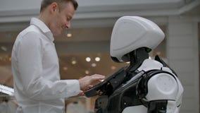 El hombre en el centro comercial comunica con un consejero del robot Vendedor moderno de la tienda y del robot El robot ayuda a u metrajes