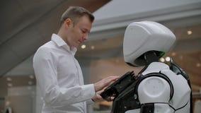 El hombre en el centro comercial comunica con un consejero del robot Vendedor moderno de la tienda y del robot El robot ayuda a u almacen de video